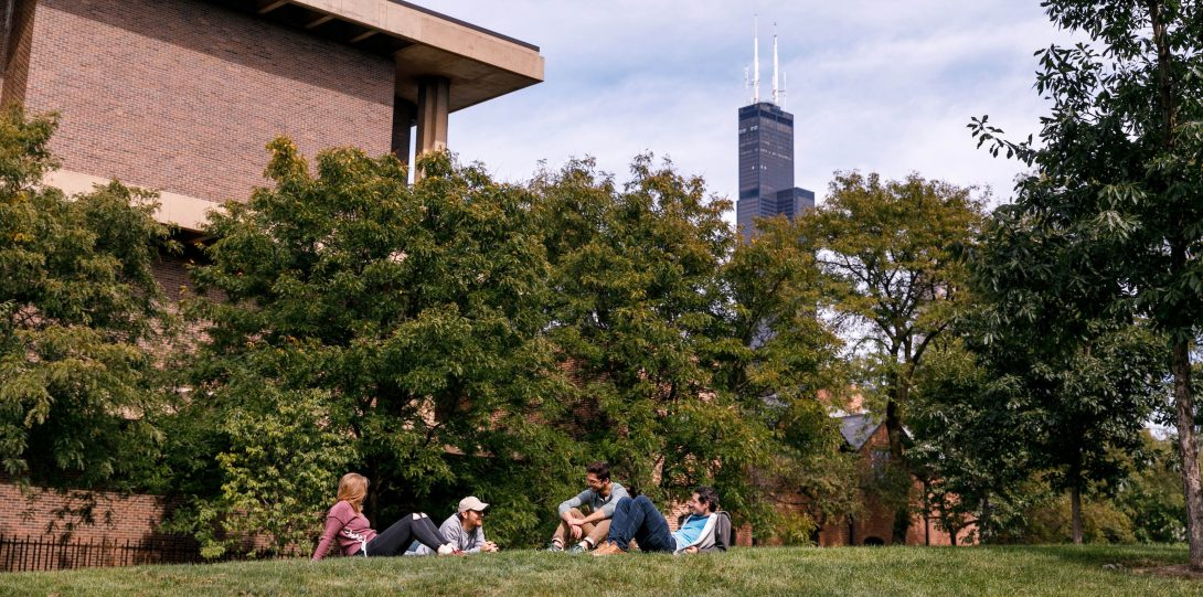 Four UIC students sit in grass on campus.